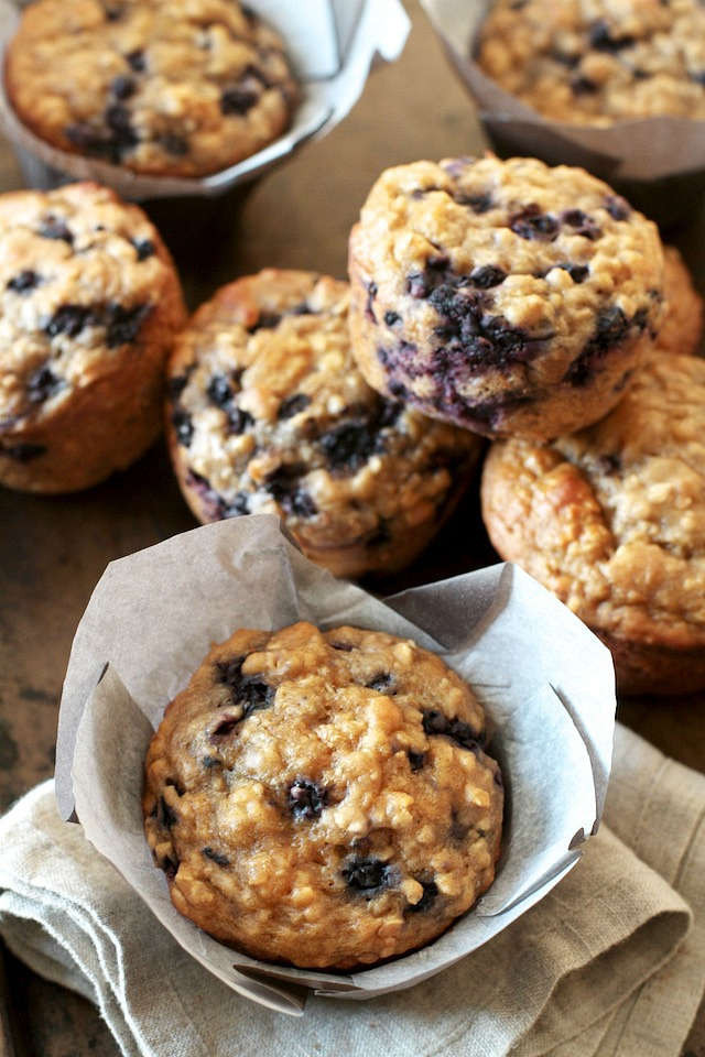 You won't find any butter or oil in these ridiculously soft and tender Blueberry Oat Greek Yogurt Muffins! What you will find is plenty of naturally sweetened, blueberry goodness in each bite!   runningwithspoons.com #healthy #muffins #breakfast #snack