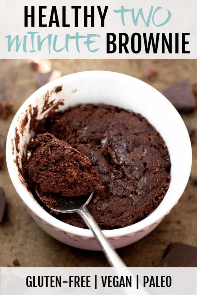 A healthy two minute brownie in a small ramekin with a spoonful laying on top.