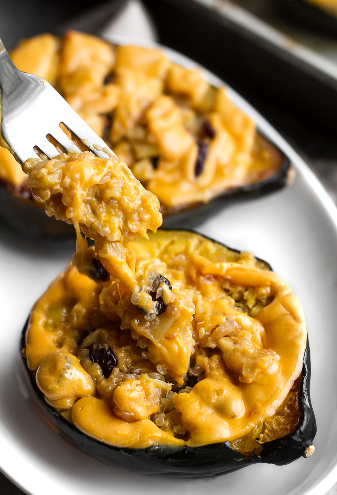 This cheezy apple cranberry quinoa stuffed squash is packed with sweet & savoury flavours and topped with an ooey, gooey, dairy-free cheese. It's healthy plant-based comfort food at its finest!   runningwithspoons.com