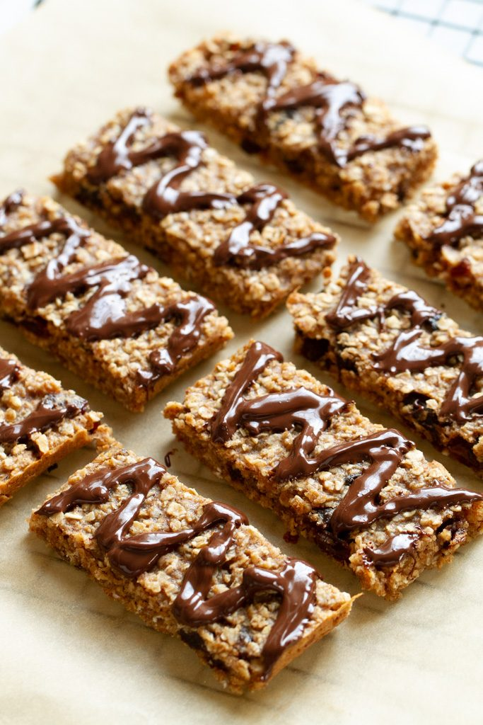 Soft and chewy granola bars cut into squares and drizzled with chocolate.