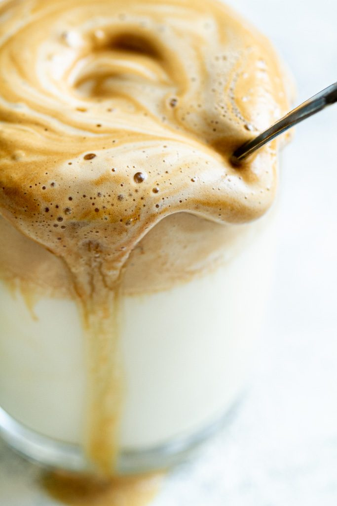 A closeup of a cup of dalgona coffee with foam dripping down the side.