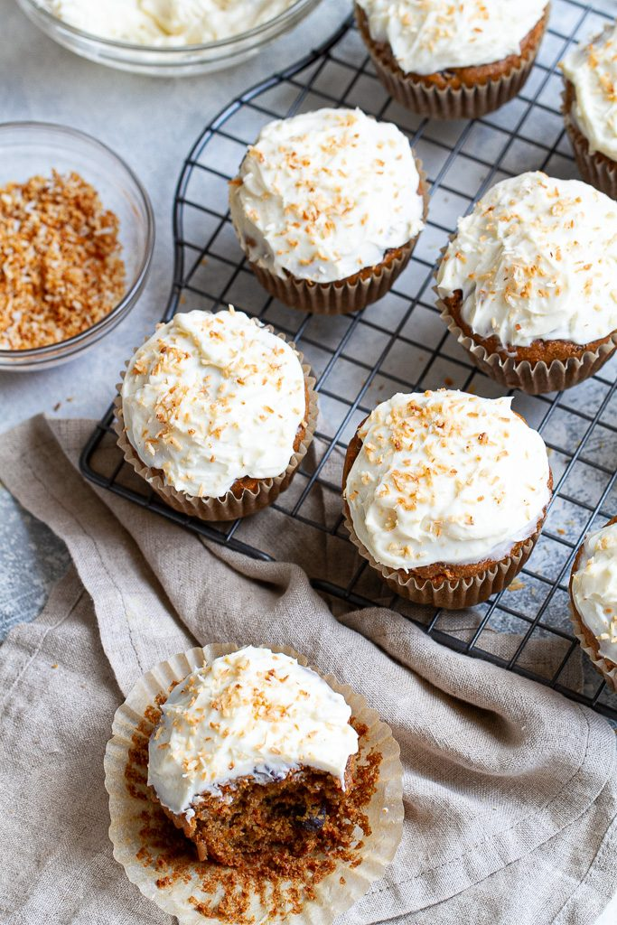 Flourless carrot cake muffins with frosting on a cooling tray.