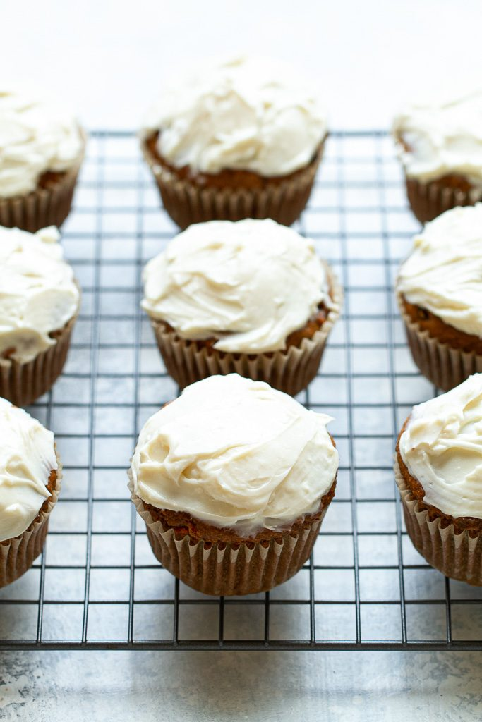 Flourless carrot cake muffins with cream cheese frosting on a cooling tray.