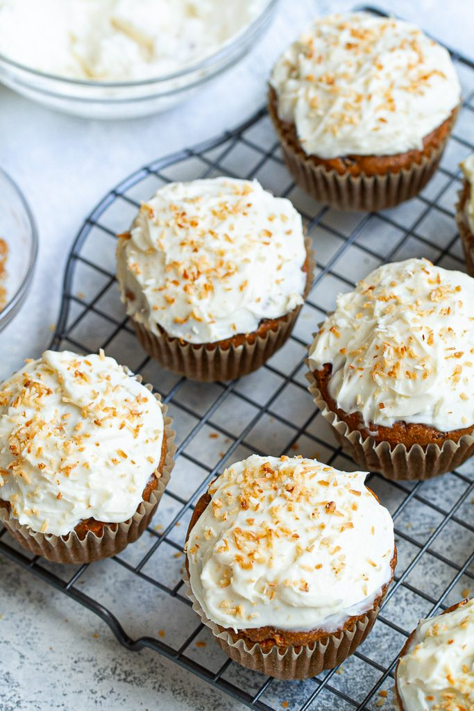Flourless carrot cake muffins with cream cheese frosting sitting on a cooling tray.