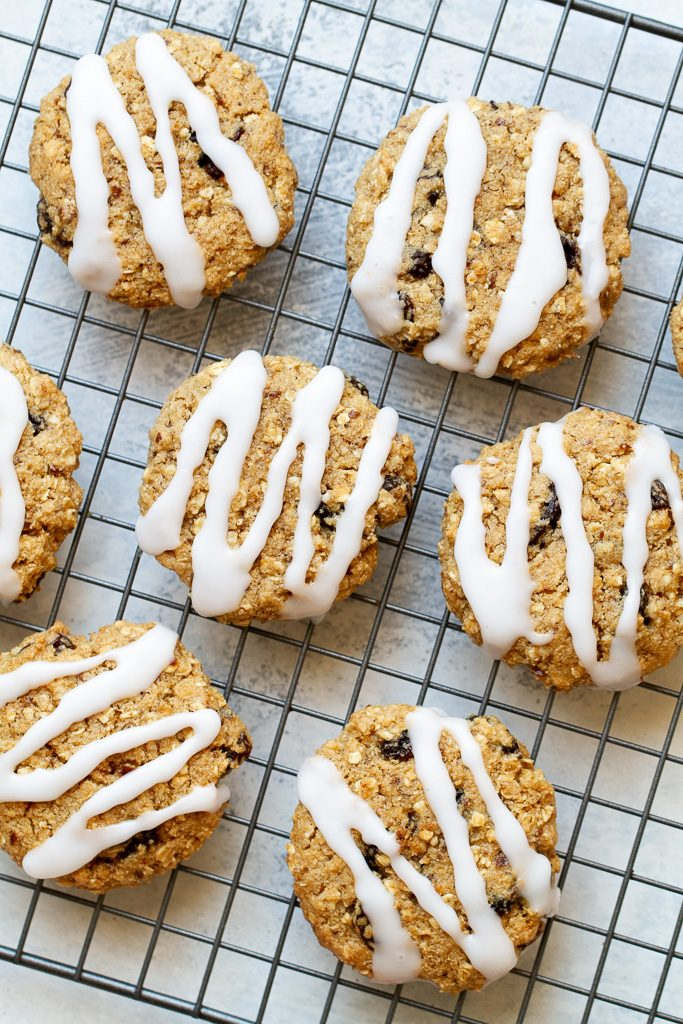 A top view of flourless oatmeal raisin cookies with icing sitting on a cooling rack.