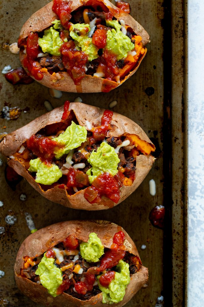 Taco stuffed sweet potatoes topped with avocado and salsa.