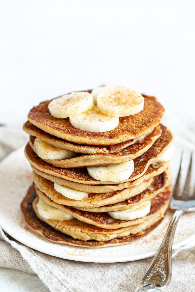 A stack of easy banana oat pancakes layered with slices of banana.
