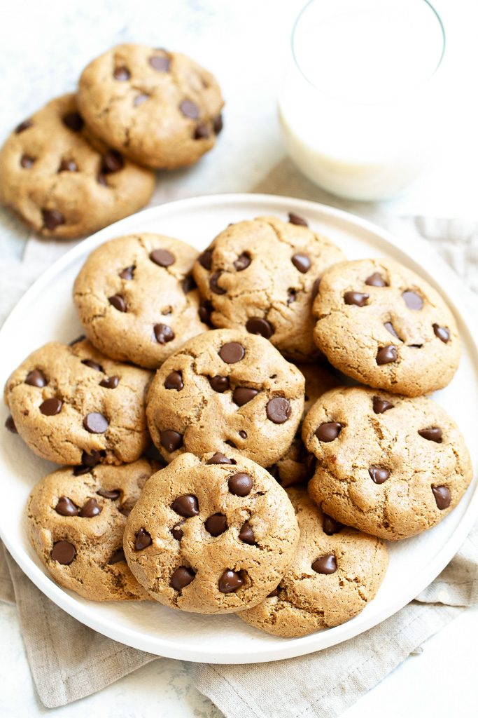 A plate of flourless chocolate chip cookies with a glass of milk.