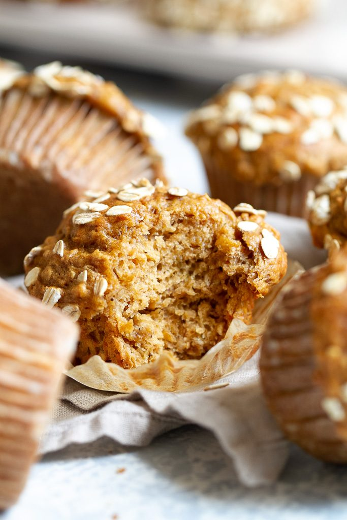A healthy banana oat muffin with a bite taken out of it so that you can see the fluffy texture inside of it.