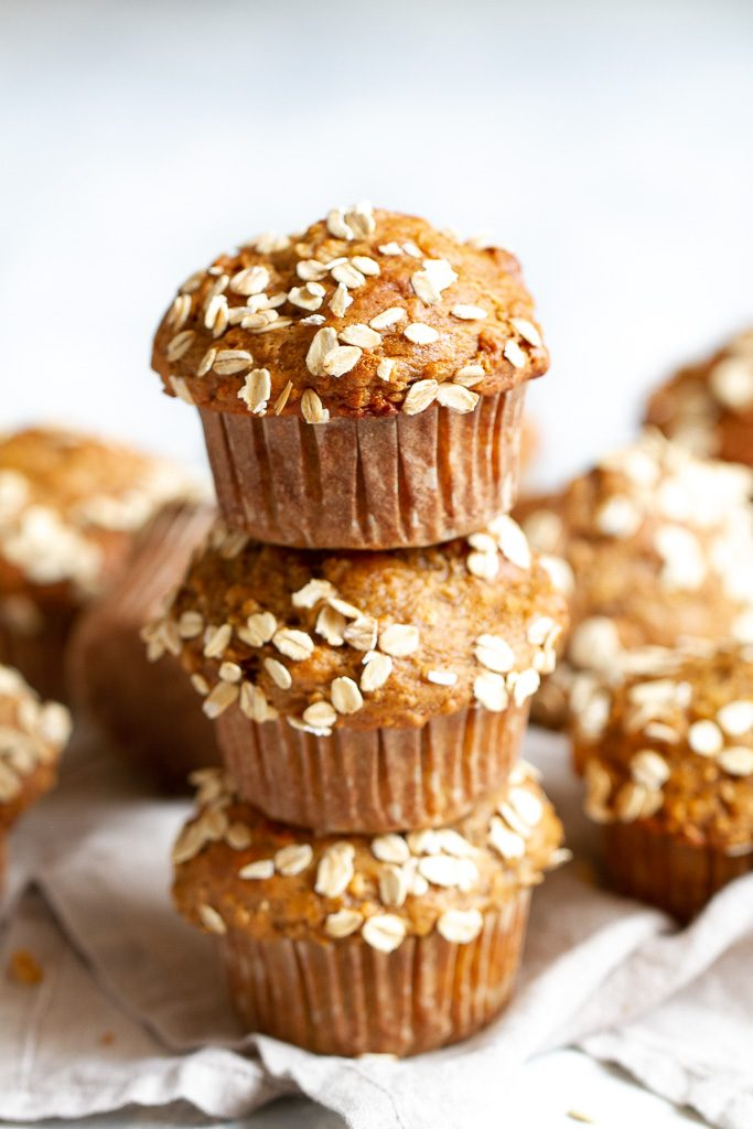 3 healthy banana oat muffins stacked on top of each other.